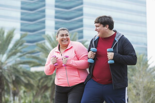 Two overweight friends exercising together, holding dumbbells, looking at each other and laughing. The Hispanic woman is in her 30s, and the man, mixed race Hispanic and Caucasian, is in his 20s.